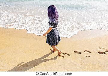 Woman walking on beach leaving footprints in the sand.