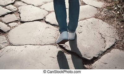 Woman walking on cobblestone pavement road, old way. Girl...