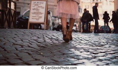 Woman walking on cobblestone pavement road in city. Girl...