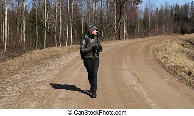 Woman walking on forest road and using binoculars