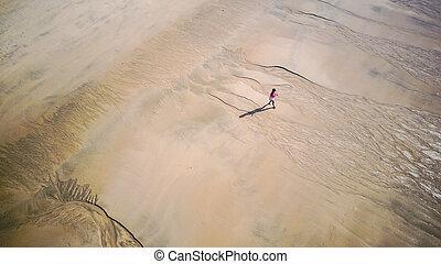 Woman walking on large beach