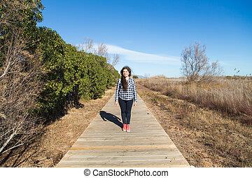 Woman walking on long wooden boardwalk trail