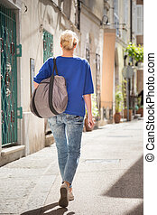 Woman walking on old cobbled street.
