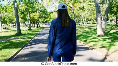 Woman walking on pathway in the park 4k - Rear view of woman...