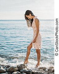 Woman walking on pebble beach