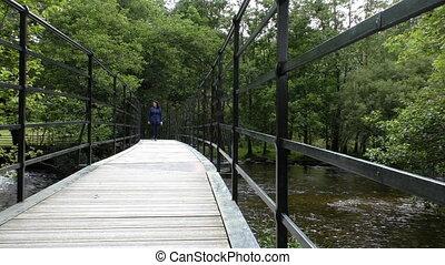 Woman walking on pedestrian bridge