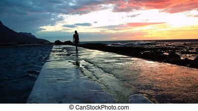 Woman walking on promenade at beach during dusk 4k - Rear...