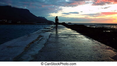Woman walking on promenade at beach during dusk 4k -...