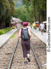 Woman walking on railway