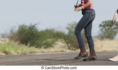 Woman walking on road in slow motion - A medium shot of a...