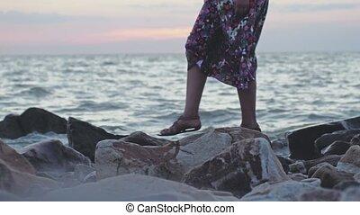 Woman walking on rocky beach in slow motion in windy weather. 3840x2160