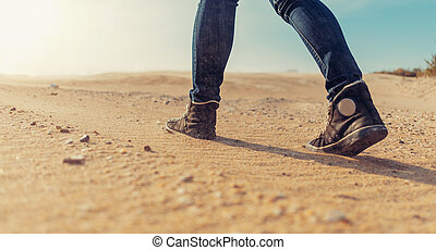 Woman walking on sand.
