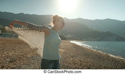 woman walking on sea shore, looking into distance, wind t-shirt
