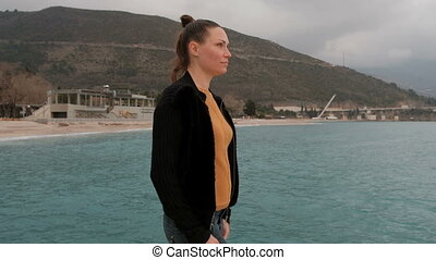 woman walking on sea shore mountains looking into distance....