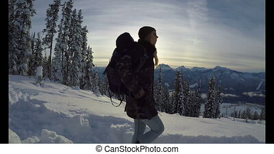 Woman walking on snow covered mountain slope 4k - Woman...
