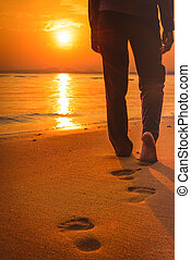 Woman walking on the beach at sunset leaving footprints over sands. Selected focus