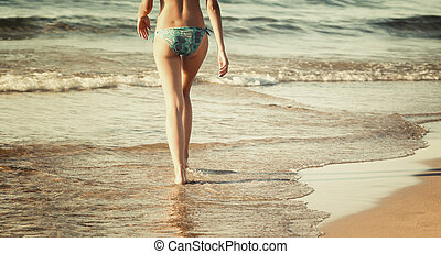Woman walking on the beach in sunset time