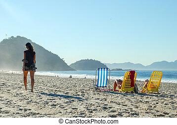 Woman walking on the beach of Copacabana, Rio de Janeiro