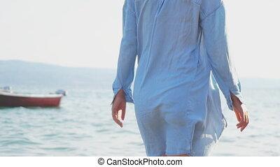 Woman walking on the beach. Rear view.