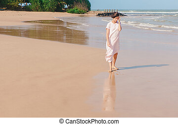 Woman walking on the beach sand