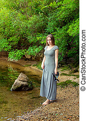 Woman walking on the river bank