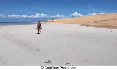 Woman Walking on White Sand Beach Leaving Footprints