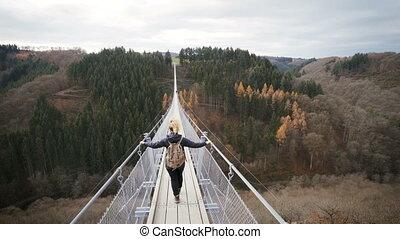 woman walking over hanging rope bridge in germany....
