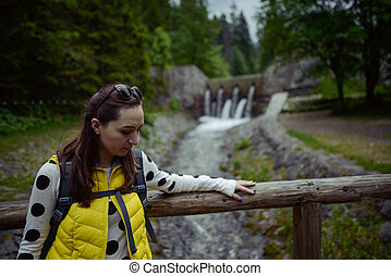 Woman walking over wooden bridge