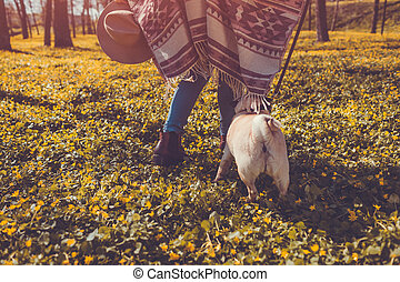 Woman walking pug dog in spring forest. Happy puppy running...