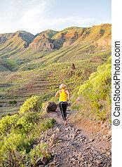 Woman walking running in rocky mountains on summer sunset