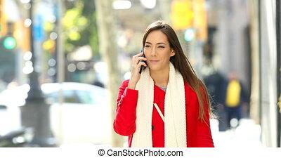 Woman walking talking on phone in the street