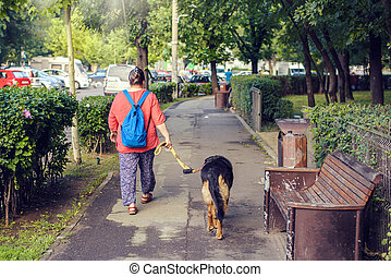 Woman walking the dog in a sunny day