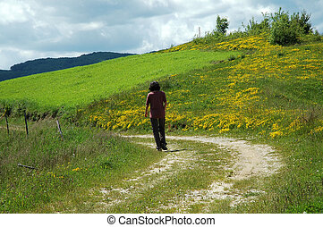 Woman walking through a meadow full with flowers