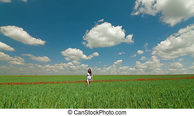 Young Woman Walking Through Green Wheat Field. Front View