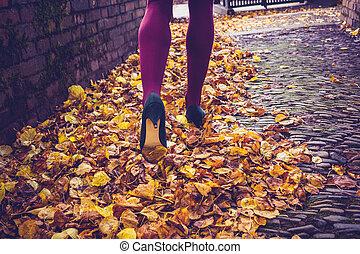 Woman walking through leaves