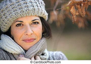Woman walking through park in autumn