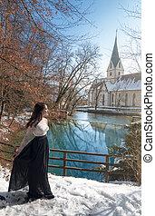 Woman walking through snow on a lakeshore