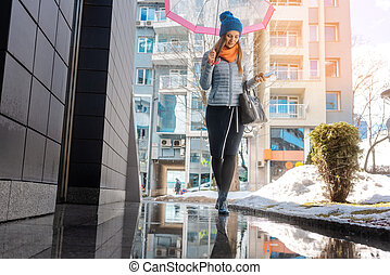 Woman walking through the city in pre-spring