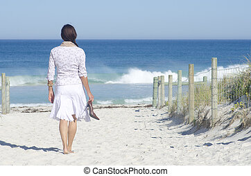 Woman walking to beach at ocean - Attractive senior woman...