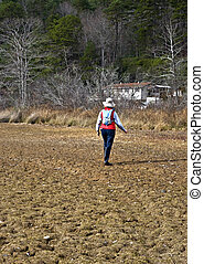 Woman Walking Toward House on Dry Cracked Ground