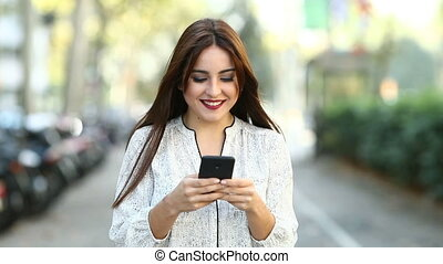 Woman walking towards camera using a smart phone