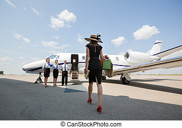 Woman Walking Towards Private Jet At Airport Terminal