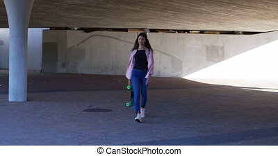 Woman walking under flyover 4k - Young woman walking under...