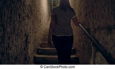 Woman walking up stairs in a dark cave alleyway - A tilting...