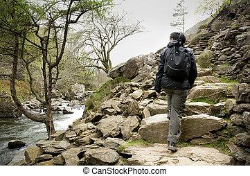 woman walking up steps of rock