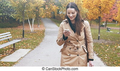 Woman walking while using her smartphone