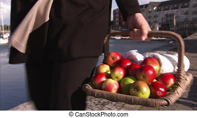 Woman walking with a basket of apples