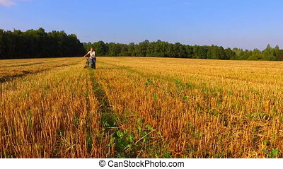 Woman walking with a bicycle by the beveled wheat field