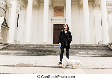 Woman walking with a dog on the street