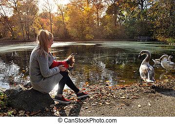Woman walking with a small dog near beautiful lake with ...